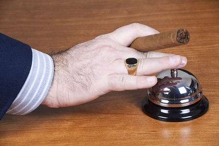 businessman waiting call: Businessman ringing a service bell.