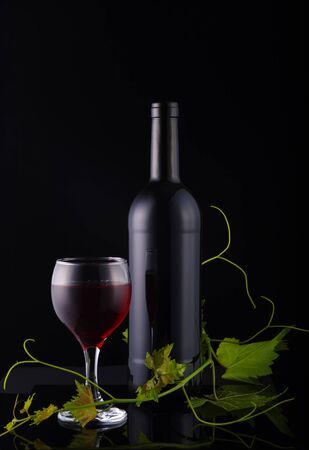 Wine bottle, glass with red wine and vine on dark glossy background.
