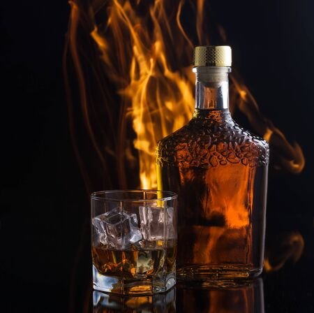Alcoholic drink in front of warm fireplace.
