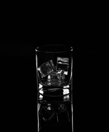 Glass with ice cubes on a black background.