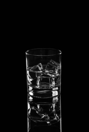 Vodka or gin tonic with ice in rocks glass on black background