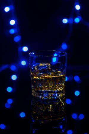Glass of whiskey on the rocks with some ice on the table.