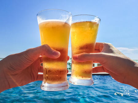 Two men enjoyed there summer vacation with their beer by poolside Stock Photo