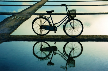 Bicycle put on surface water, water surface like mirror that reflect it photo