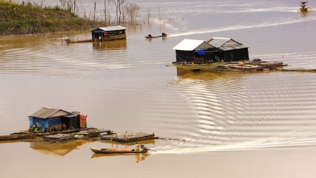 lake dwelling:  the scene of fisherman coming their lake dwelling by motor-boat at fishing village create ripplings on the water suface is so lively  This fishing village locate at NamKa lake, Dalak