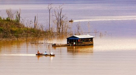 lake dwelling:    At Nam Ka lake, Daklak, where is people live on their houseboat, everyday they make their living by fishing, in evening, lake-dwelling row their boat come lake dwelling, their live really peaceful, charming, serene, calm                           Stock Photo