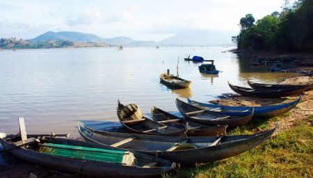at Lak lake, small bamboo crafts lay on the shore under sunlight  That make beautiful, peaceful landscape  This lake is where many fishing boat rowing everyday, after work they were attached to the border  photo