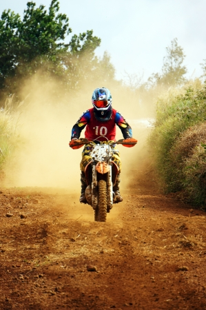 The motorcycle race hole on December at Dambri waterfall, motorcyclist try to speed up goal, red soil way, indistinct dust photo