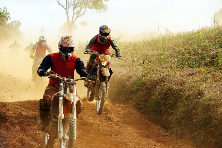 The motorcycle race hole on December at Dambri waterfall, motorcyclist try to speed up goal, red soil way, indistinct dust