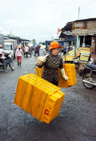 seafish: The women with tired face rattan plastic tray into market, she wear yellow hat, step on marshy  July 15, 2013