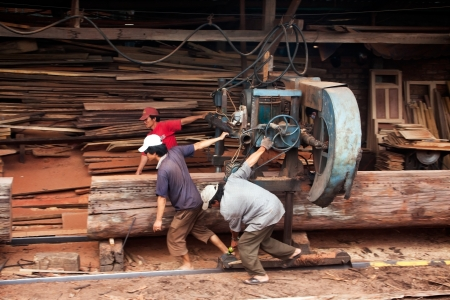Three woodworker try to pull cumbersome machine to split section of a tree trunk into plank at sawmill  June 18, 2012
