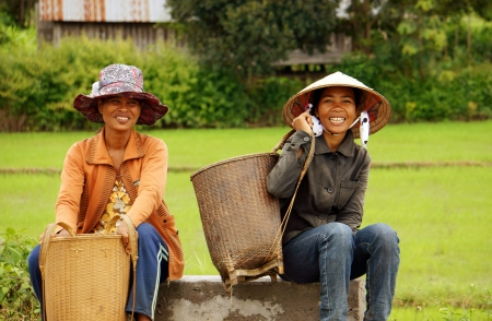 nurseryman: Two woman wear hat , carry papoose ( gui) with smile on face, sit and wait on roadside at golden light evening. September 5, 2012 Editorial