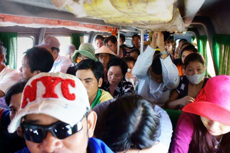 assign: People sit in overcrowded, packed like sardines with number of passenger over assign, they look unhappy on non-stop express passenger boat. June 29, 2013