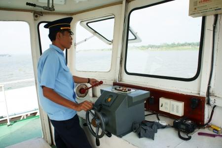 フェリー ボートのキャビン、ferryman 摩耗のユニフォームは川を渡る交通機関の乗客にホイールを制御します。ドンタップで水平フレームの色で取る  報道画像