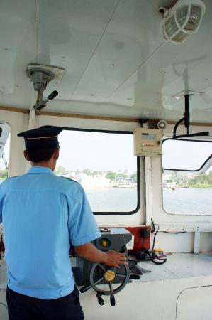 フェリー ボートのキャビン、ferryman 摩耗のユニフォームは川を渡る交通機関の乗客にホイールを制御します。ドンタップ、垂直フレームの色で取る  報道画像