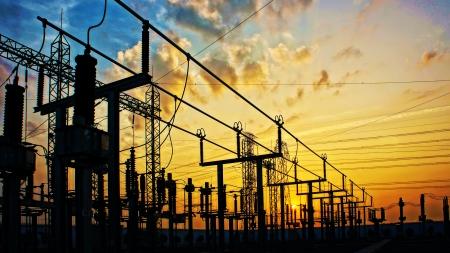 日の出の変圧器の場所、黄色い空まで高電圧で印象ネットワーク。 写真素材