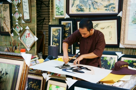 ideograph: Scene of the calligrapher draw handwriting in penmanship at fair in springtime, this is special culture of Vietnamese when Tet come. In colorful, horizontal frame, February 1, 2013