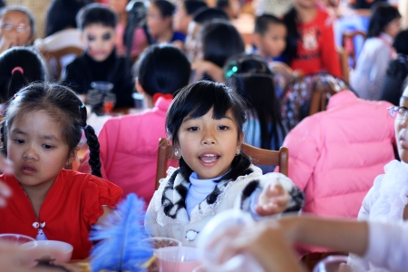 Little girl with her classmate at party in the occasion of Halloween festival hole on by international school. October 30, 2011
