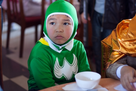 Schoolboy disguise oneself as a batman, he wears green clothes, sit at party on the occasion of Halloween festival hole on by international school  October 30, 2011