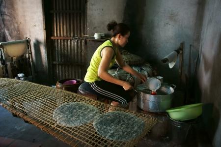 girdle: Woman make girdle cake  banh trang  - is the usual rice flour Editorial