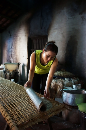traditon: Woman make girdle cake  banh trang  - is the usual rice flour Editorial