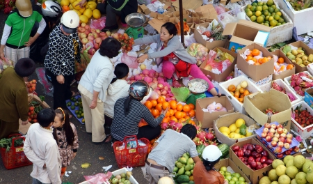 vendee: People sell and buy fruit at open air market, there
