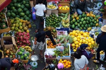 People sell and buy fruit at open air market, Dalat, Viet Nam- February 8, 2013