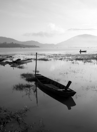 The quiet lake in early morning with black   white tone, fishermen make living on there, boat reflect on surface water photo