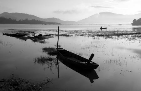 The quiet lake in early morning with black   white tone, fishermen make living on there, boat reflect on surface water Stock Photo - 23117013
