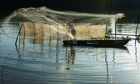 Beatutiful landcape with reflection of silhouette of fisherman cast a net on river surface water photo