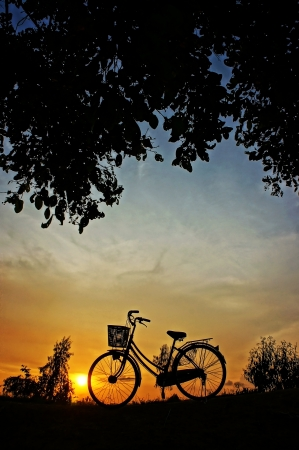 Beautiful landscape of nature with impression of the sun  and silhouette of bicycle  in sunset at countryside