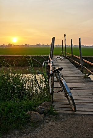 Beautiful landscape of nature with lovely orange sunset, bicycle put up on wooden fence, small wooden bridge across a river and in the distance is green rice field  photo