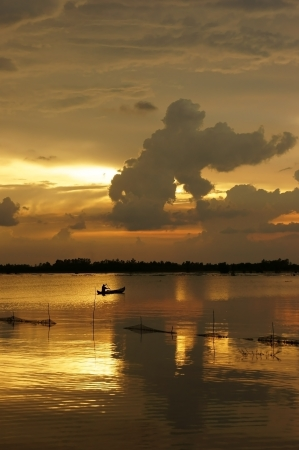 People rowing the row boat on river  at sunrise, cloudscape with clouds as gorilla shape on the yellow sky Stock Photo - 23955197