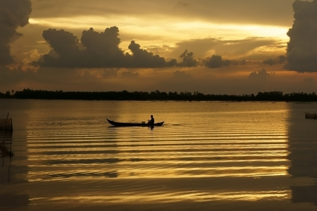 People rowing the row boat on golden surface water of river at sunrise, clouds reflect on water make a rectangle frame    Stock Photo - 23955199