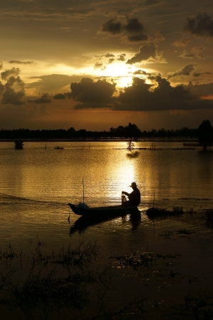 Fisherman on rowboat do fishing on river in flood season at sunrise  Stock Photo - 23955200
