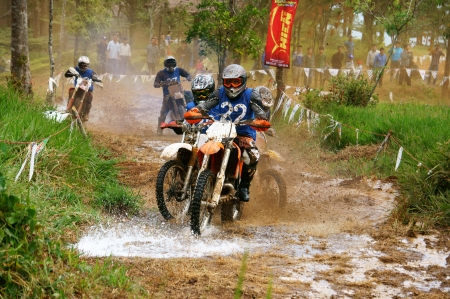 loc: BAO LOC, VIET NAM- DECEMBER 23:  Racer in activity at motorcycle race hole on Bao Loc, Viet Nam, they try to across a marshy stretch of road with violent competition in December 23, 2012                Editorial