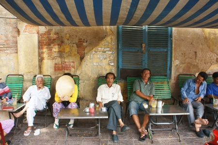 SAI GON, VIET NAM- APRIL 12: People sitting in make shift shop coffee on pavement to have breakfast, this is specific habit of Vietnamese  Viet Nam on April 12, 2013
