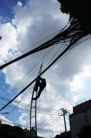 Electrician working among electric wire network in the blue sky as spider      photo