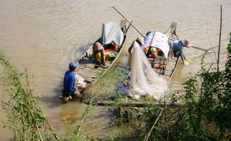 Families of fisherman do fishing on river, on the row boat, husban cast a net, his wife do fish in clean, children play alone in Hong Ngu, Viet Nam on Nov 12, 2013
