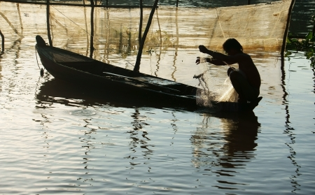 silhouette   s fisherman sitting on row boat, pick up the net, repair for fishing to catch fish on river at morning in flood season