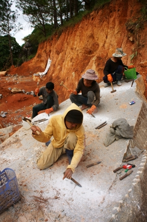 roadworks:  Worker swith splitter and hammer on hand try to carve out  large stone into small size for road-works at mountain pass in Lam Dong, Viet Nam in November 28, 2013