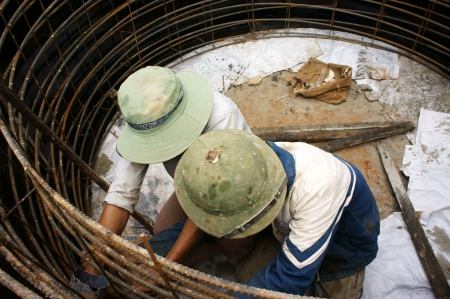 roadworks:  Workers casting cement culvert for road-works by steel circular mould at mountain pass in Lam Dong, Viet Nam in November 28, 2013