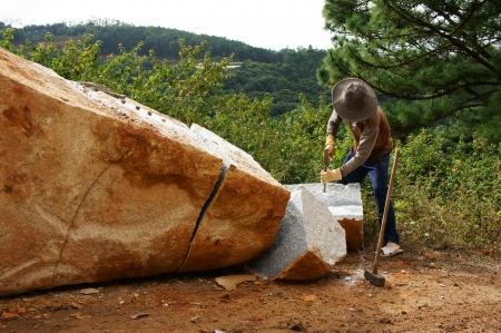 roadworks:  Worker with splitter on hand try to split large rock into small size for road-works at mountain pass in Lam Dong, Viet Nam in November 28, 2013