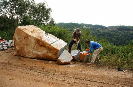 roadworks:  Two Workers with splitter on hand try to split large rock into small size for road-works at mountain pass in Lam Dong, Viet Nam in November 28, 2013