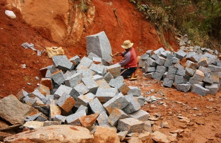 roadworks:  Worker with splitter on hand try to split stone into rectangle shape for road-works at mountain pass in Lam Dong, Viet Nam in November 28, 2013