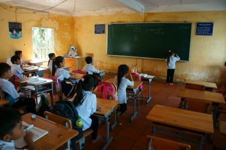 schooler: Concentrato primario pupilla in orario scolastico della scuola primaria, una scrittura alunno sulla lavagna a Long An, Vietnam su Nov 11, 2013