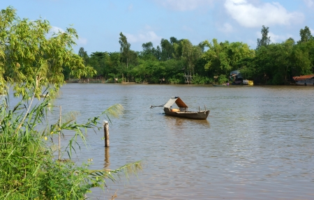 waterway: Lonely Wooden Rowb0oat float on river, the river enclosed by green trees make calm, tranquil scenic of the waterway- Mekong Delta