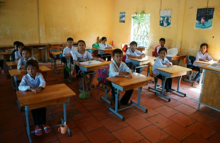 Primary pupil listening with concentration in classroom of primary school in Long An, Viet Nam on Nov 11, 2013
