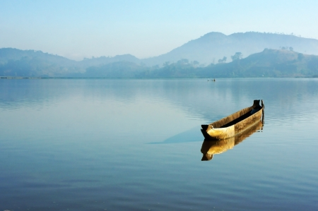 Charming landscape of nature with  wooden boat (dug-out canoe ) floating alone and reflect on surface water of lake, behind of lake moutain