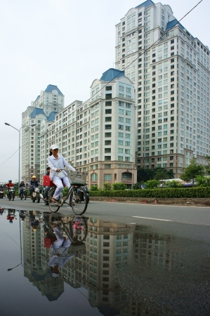 HO CHI MINH, VIET NAM- DEC 15: People ride bicycle on street with high-class high-rise building background, the building reflect on surface water on street  in Ho Chi Minh, Viet Nam on Dec 20, 2013